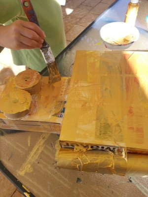 We used gold paint but yellow will still look great. We only did one coat but you may like to do 2 to get rid of the background on the boxes
